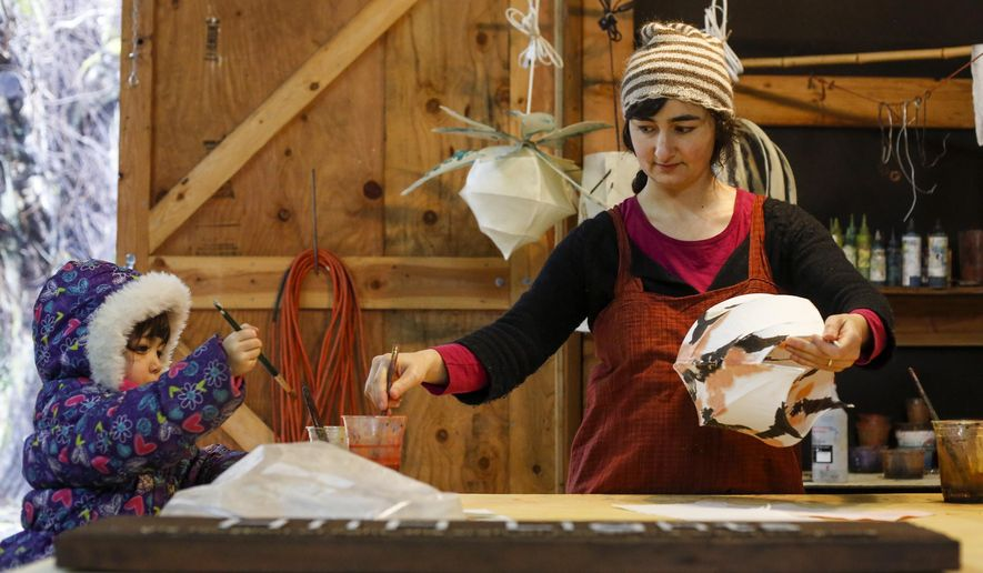 In this photo taken on Monday, Jan. 5, 2015, Kestrel Gates, right, paints a light in the barn studio while her daughter, Mai Linh Quang, paints a strip of paper in Astoria, Ore. Gates uses primarily airbrush paints for the lights but also uses indigo and a handmade walnut paint. (AP Photo/The Daily Astorian, Joshua Bessex)