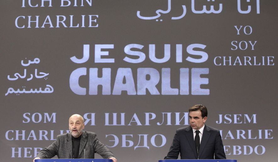 """The Brussels International Press Association President Tom Weingaertner, left, and European Commission Chief Spokesperson Margaritis Schinas address the media in front of a banner that reads: """"Je suis Charlie (I Am Charlie)"""", as they pay respect for the victims of Wednesday's terror attack in Paris, at the European Commission headquarters, in Brussels, Thursday, Jan. 8, 2015. Eight journalists, two police officers, a maintenance worker and a visitor were killed, and eleven people wounded in a terrorist attack against French satirical newspaper Charlie Hebdo in Paris. (AP Photo/Yves Logghe)"""