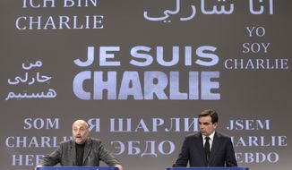 "The Brussels International Press Association President Tom Weingaertner, left, and European Commission Chief Spokesperson Margaritis Schinas address the media in front of a banner that reads: ""Je suis Charlie (I Am Charlie)"", as they pay respect for the victims of Wednesday's terror attack in Paris, at the European Commission headquarters, in Brussels, Thursday, Jan. 8, 2015. Eight journalists, two police officers, a maintenance worker and a visitor were killed, and eleven people wounded in a terrorist attack against French satirical newspaper Charlie Hebdo in Paris. (AP Photo/Yves Logghe)"