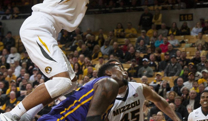 Missouri's Johnathan Williams III, top, dunks the ball over LSU's Brian Bridgewater, bottom, as he follows a shot by Missouri's Keanau Post (45) during the first half of an NCAA college basketball game Thursday, Jan. 8, 2015, in Columbia, Mo. (AP Photo/L.G. Patterson)