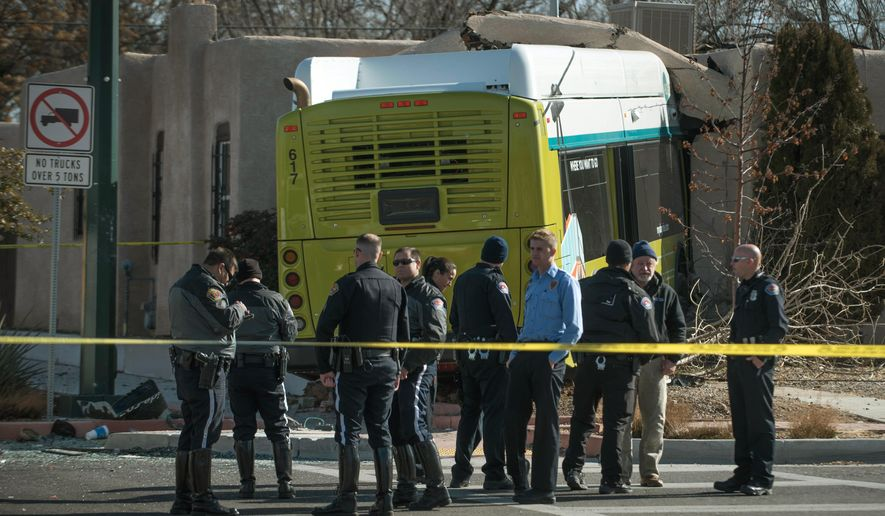 Police and investigators work the scene where a bus driver crashed into a house after hitting a commercial vehicle that ran a red light at an intersection, Thursday, Jan. 8, 2015, in Albuquerque, N.M. Up to eight people were taken to a hospital after the incident. (AP Photo/The Albuquerque Journal, Roberto E. Rosales)