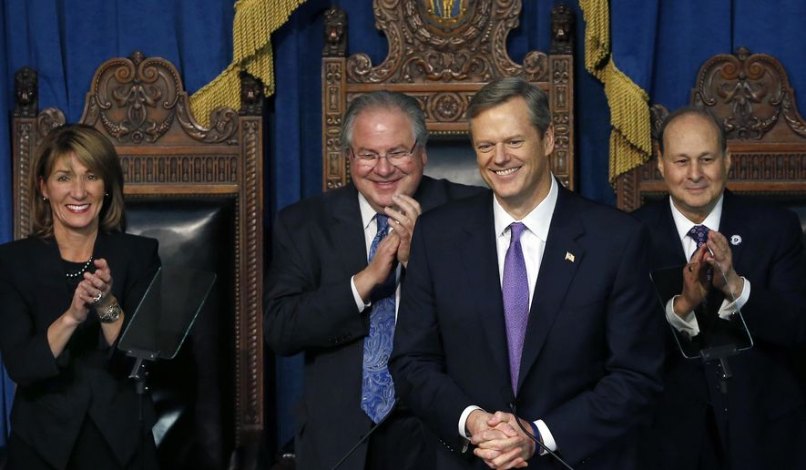 Charlie Baker receives applause after being sworn in as governor of Massachusetts by Mass. Senate President Stanley Rosenberg, far right, while House Speaker Robert DeLeo and Mass. Lt. Gov. Karen Polito applaud, at left, at the Statehouse in Boston, Thursday, Jan. 8, 2015. (AP Photo/Elise Amendola)
