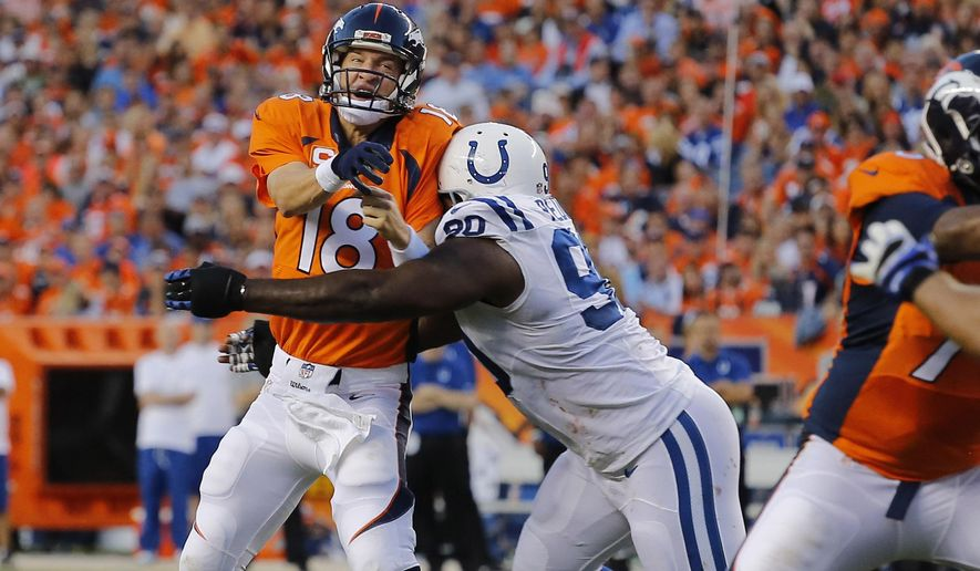 FILE - In this Sept. 7, 2014, file photo, Denver Broncos quarterback Peyton Manning (18) throws a touchdown pass as he is hit by Indianapolis Colts' Cory Redding during the first half of an NFL football game in Denver. The Colts know what they must do to beat the Broncos _ pressure Peyton Manning. (AP Photo/Jack Dempsey, File)