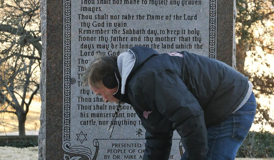 Mike Sanford, the contractor who placed the foundation for the Ten Commandments Monument, sweeps in front of the monument after the replacement was installed at the state Capitol in Oklahoma City, Thursday, Jan. 8, 2015. The original monument, which is at the center of a lawsuit, was smashed into pieces in October when someone drove a car across the Capitol lawn and crashed into it. (AP Photo/Sue Ogrocki)