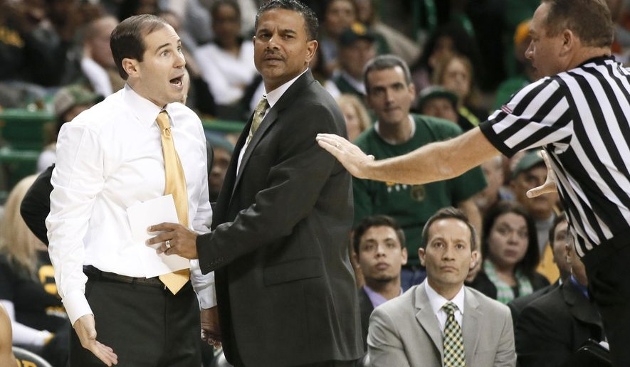 Baylor head coach Scott Drew is held back by assistant coach Jerome Tang, center, as Drew protests  a foul against his team in the second half of an NCAA college basketball game against Kansas, Wednesday, Jan. 7, 2015, in Waco, Texas. Kansas won 56-55. (AP Photo/Tony Gutierrez)
