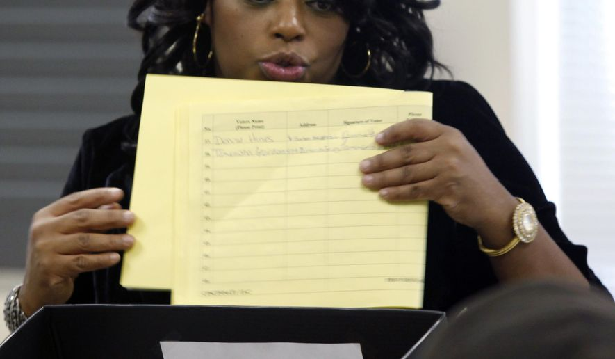 FILE - In this Tuesday, Nov. 6, 2012 file photo, precinct worker Crystal Wright gives instructions to voters who were told they needed to vote with a provisional ballot at the Urban League in the Avondale section of Cincinnati. A report from the state's elections chief shows Ohio voters cast fewer provisional ballots, and a higher percentage of those were counted in the last election. (AP Photo/The Cincinnati Enquirer, Carrie Cochran, File) MANDATORY CREDIT; NO SALES