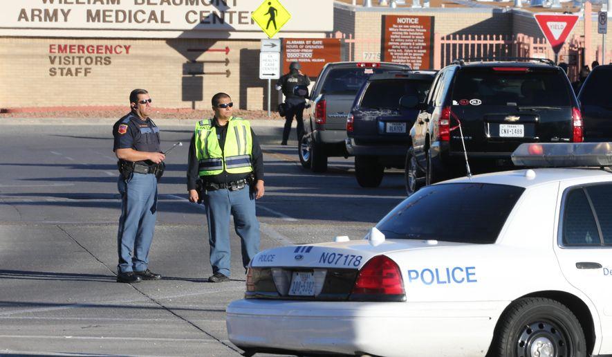 CORRECTS YEAR - Police officers guard an entrance to the Beaumont Army Medical Center/El Paso VA campus during the search for a gunman Tuesday, Jan. 6, 2015. (AP Photo/The El Paso Times, Victor Calzada)