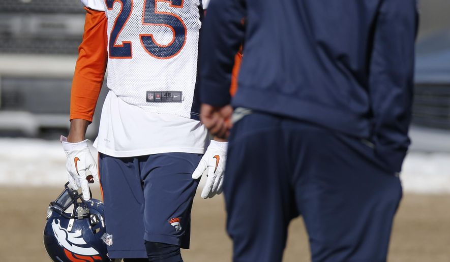 Denver Broncos cornerback Chris Harris Jr., back, jokes with a coach during a team practice for an NFL football divisional playoff game against the Indianapolis Colts Thursday, Jan. 8, 2015, in Englewood, Colo. (AP Photo/David Zalubowski)