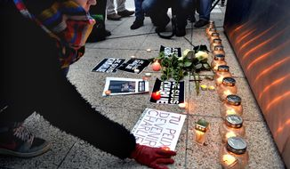 A woman puts a candle on the ground as she attends a ceremony to pay tribute to victims of the attack against the French satirical weekly Charlie Hebdo, in front of the French Institute in Budapest, Hungary, Thursday, Jan. 8, 2015, a day after 12 people were slain by two armed men who stormed the Paris offices of the magazine. (AP Photo/MTI, Zoltan Mathe)