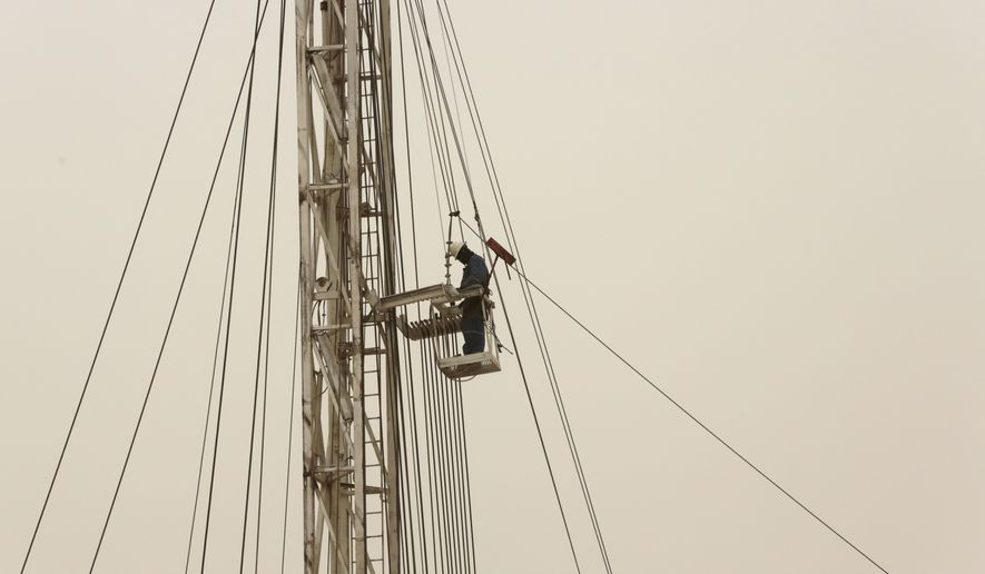 An oil man works on a new oil rig during a sandstorm that blew in on Thursday, Jan. 8, 2015, in the desert oil fields of Sakhir, Bahrain. Global stock markets rose Thursday, boosted by positive economic news from the U.S., expectations of stimulus in Europe and stabilization in oil prices after sharp falls. (AP Photo/Hasan Jamali)