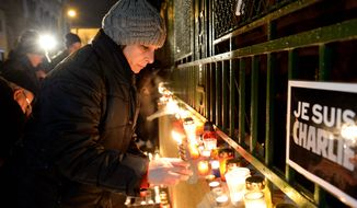 "People light candles as they pay tribute to victims of the attack against the French satirical weekly Charlie Hebdo, in front of the French embassy in Budapest, Hungary, on Thursday, a day after 12 people were slain by two armed men who stormed the Paris offices of the magazine. Inscriptions read ""I am Charlie"". (Associated Press)"
