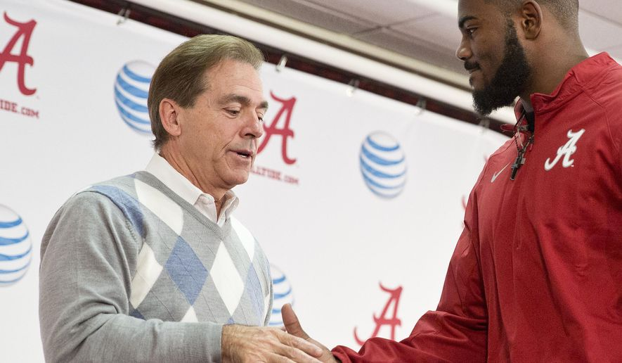 Alabama head coach Nick Saban shakes Landon Collins hand after Collins spoke to the press about his decision to enter the NFL draft during a press conference, Friday, Jan. 9, 2015, in Tuscaloosa, Ala. (AP Photo/Brynn Anderson)