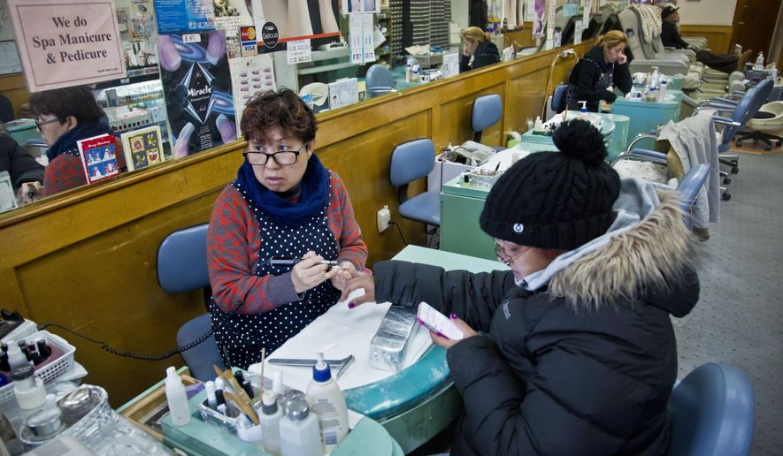 "Lisa Moon, left, owner of Castle nail salon, manicures a customer at her the salon she has owned for 16 years without ""complaints,"" Thursday, Jan. 8, 2015, in New York. Dirty nail clippers could get the same treatment as spoiled food under a proposal to expand New York City's restaurant letter-grade system to a new frontier: barbershops, hair salons and nail salons. (AP Photo/Bebeto Matthews)"