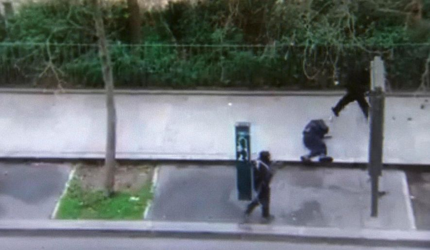 In this image made from amateur video recorded on Wednesday, Jan. 7, 2015 by Jordi Mir, masked gunman walk past a police officer moments after shooting him at blank range outside the offices of French satirical newspaper Charlie Hebdo in Paris. Paris residents captured chilling video images of two masked gunmen shooting a police officer after an attack at a French satirical newspaper. In the video, the gunmen armed with assault rifles are seen running up to an injured police officer, who lies squirming on the ground. The police officer raises his hands up before one of the assailants shoots him in the head at a close range. (AP Photo/Jordi Mir) NO SALES