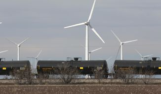 In this photo made Monday, Dec. 22, 2014, oil tankers train cars ride past windmills neat Sweetwater, Texas. Sweetwater is bracing for layoffs and budget cuts, anxious as oil prices fall and its largest investors pull back. (AP Photo/LM Otero)