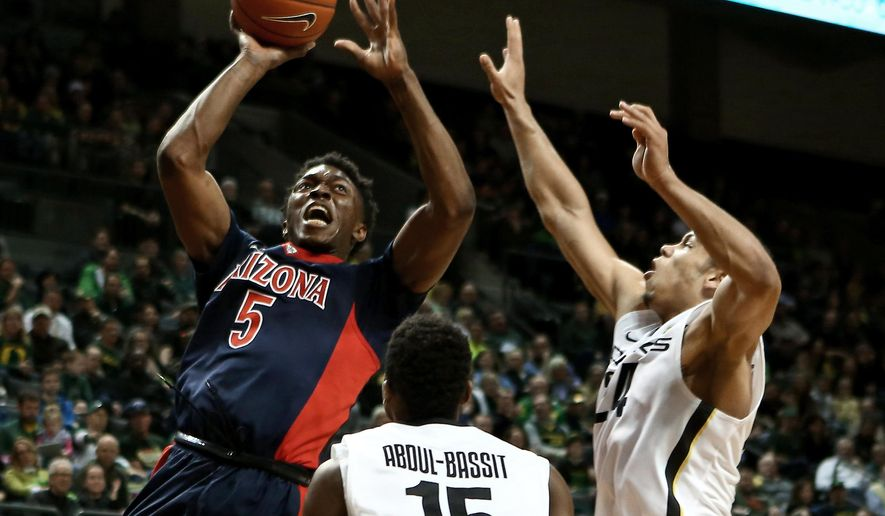 Arizona forward Stanley Johnson shoots over Oregon guard Jalil Abdul-Bassit, center, and forward Dillon Brooks, right, during the first half of an NCAA college basketball game Thursday, Jan. 8, 2015, in Eugene, Ore. (AP Photo/Ryan Kang)