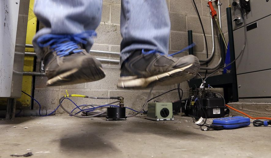 "As several pieces of seismic monitoring equipment sit on the floor, a scientist does a ""stomp test"" to check the gear at the Seattle Seahawks' field, CenturyLink Field, Thursday, Jan. 8, 2015, in Seattle. Scientists with the Pacific Northwest Seismic Network installed the instruments to record expected vibrations from jumping and stomping fans at Saturday's Seahawks playoff game against the Carolina Panthers. The work follows the ""beast quake"" that was generated by a Marshawn Lynch ""Beast Mode"" touchdown run on Jan. 8, 2011, and recorded on a seismometer in Seattle. (AP Photo/Elaine Thompson)"