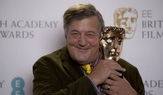 British comedian and actor Stephen Fry poses for photographs with a BAFTA (British Academy of Film and Television Arts) statuette. (AP Photo/Matt Dunham)