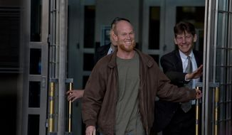 In this Thursday, Jan. 8, 2015, photo, Eric McDavid, 37, walks out of the Federal Courthouse in Sacramento with his attorney's Ben Rosenthal and Mark R. Vermeulen, right, after being released from prison. McDavid, the California man considered by the federal government to be a radical eco-terrorist and a threat to the nation, was set free after nearly nine years in prison when the government conceded that thousands of pages of evidence were never turned over to his defense attorney. (AP Photo/Sacramento Bee, Jose Luis Villegas) MAGS OUT; LOCAL TELEVISION OUT (KCRA3, KXTV10, KOVR13, KUVS19, KMAZ31, KTXL40); MANDATORY CREDIT