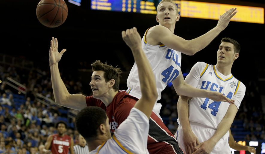 Stanford forward Rosco Allen shoots between UCLA guard Noah Allen, bottom, forward Gyorgy Goloman, right, and center Thomas Welsh during the first half of an NCAA college basketball game in Los Angeles, Thursday, Jan. 8, 2015. (AP Photo/Chris Carlson)