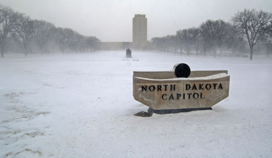 High winds and blowing snow obscure the state Capitol in Bismarck, N.D., Thursday, Jan. 8, 2015. (AP Photo/The Bismarck Tribune, Tom Stromme)