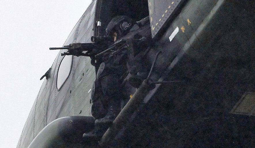 Armed securtiy forces fly overhead in a military helicopter  in Dammartin-en-Goele, northeast of Paris, Friday Jan. 9, 2015.   French security forces swarmed this small industrial town northeast of Paris Friday in an operation to capture a pair of heavily armed suspects in the deadly storming of a satirical newspaper. (AP Photo/Thibault Camus)