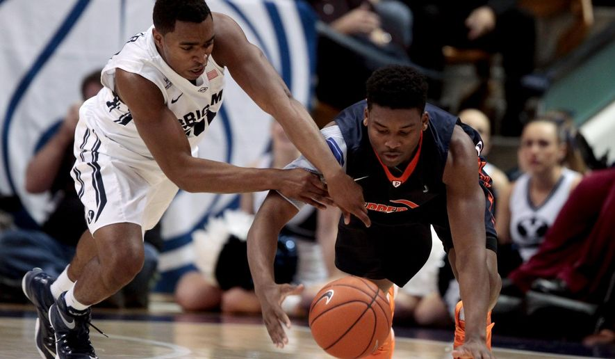 BYU guard Anson Winder, left, and Pepperdine guard Marley Biyendolo dirve for a loose ball during an NCAA college basketball game Thursday, Jan. 8, 2015, in Provo, Utah. (AP Photo/Daily Herald, Ian Maule)