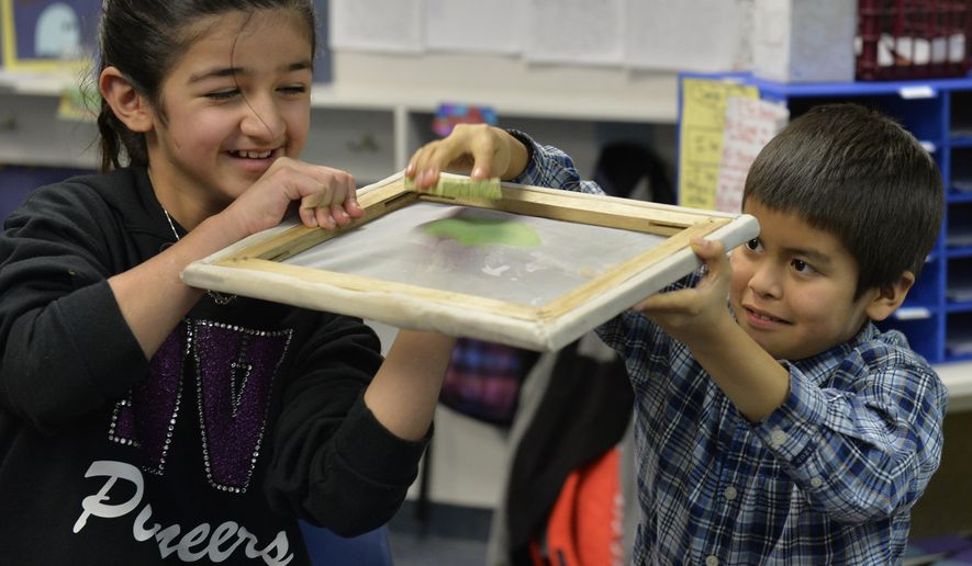 In this photo taken on Wednesday, Jan. 7, 2015, fourth graders Aaliyah Abassi, 10, left, and Nathan Roberts, 9, learn how to make new paper out of recycled paper at Everson Elementary School in Everson, Wash. The class was part of learning about waste prevention. (AP Photo/The Bellingham Herald, Philip A. Dwyer)