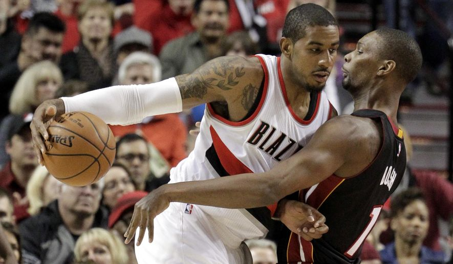 Portland Trail Blazers forward LaMarcus Aldridge, left, drives against Miami Heat center Chris Bosh during the first half of an NBA basketball game in Portland, Ore., Thursday, Jan. 8, 2015. (AP Photo/Don Ryan)
