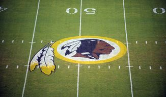 In this Aug. 28, 2009 file photo, the Washington Redskins logo is seen on the field before the start of a preseason NFL football game in Landover, Md. The Justice Department says it is intervening in a trademark dispute concerning the team name of the Washington Redskins. A June ruling from the U.S. Patent and Trademark Office stripped the professional football team of trademark protection,  (AP Photo/Nick Wass, File)