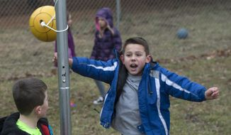 Austin Bryant celebrates his victory at tetherball with Hogan Conder during recess at Marlin Elementary School in Bloomington, Ind. (Associated Press)