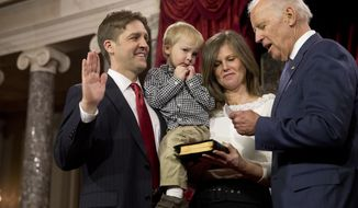 Vice President Joe Biden administers the Senate oath to Sen. Ben Sasse, R-Neb., holding his son Augustin, next to wife Melissa Sasse, during a ceremonial re-enactment swearing-in ceremony, Tuesday, Jan. 6, 2015, in the Old Senate Chamber of Capitol Hill in Washington. (AP Photo/Jacquelyn Martin)