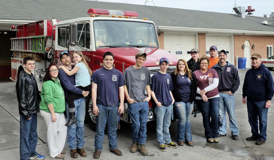 Garrett Hodgson, Cassidi Taylor, Josh Taylor, Kennadi Taylor, Caleb Belford, Corry Sine, Bryan Kerns, Amber Keller, Tyler Stottlemyer, Courtney Taylor, Matt Wyne, Matt Taylor and Roger Milburn, all members of North Mountain Volunteer Fire and Rescue near Winchester, Va., pose for a group photo in front of the fire station on Sunday, Jan. 4, 2015. They are among seven family units of roughly 30 total volunteers at North Mountain. (AP Photo/The Winchester Star, Scott Mason)
