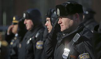 Philadelphia police officers salute while the National Anthem is sung during a pro-police rally, Saturday, Jan. 10, 2015, on Independence Mall in Philadelphia. Organizers called the gathering the Delaware Valley Pro-Blue Rally and said that the event was in remembrance of fallen New York City police officers Rafael Ramos and Wenjian Liu. (AP Photo/ Joseph Kaczmarek)
