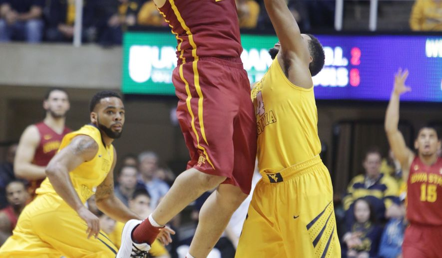 Iowa State guard Abdel Nader (2) passes the ball over West Virginia guard Gary Browne (14) during the second half of an NCAA college basketball game, Saturday, Jan. 10, 2015, in Morgantown, W.Va. Iowa defeated West Virginia 74-72. (AP Photo/Raymond Thompson)