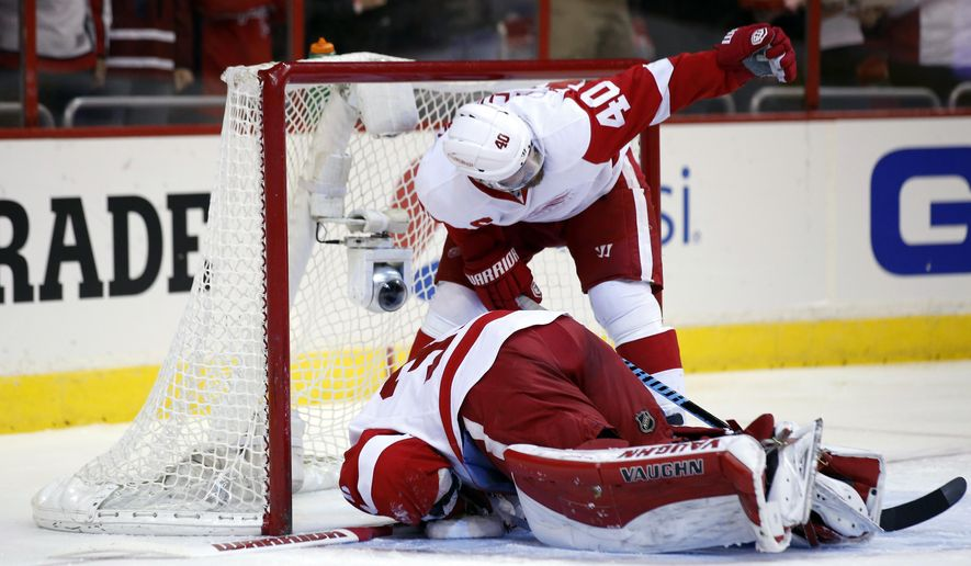 Detroit Red Wings left wing Henrik Zetterberg (40), from Sweden, calls for help after goalie Jimmy Howard was injured in the first period of an NHL hockey game against the Washington Capitals, Saturday, Jan. 10, 2015, in Washington. Howard was taken away on a stretcher for a groin injury. (AP Photo/Alex Brandon)
