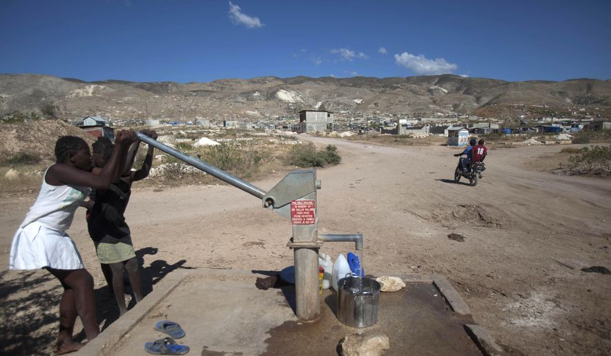 Children pump water from a well at their new community in the arid hills north of the Capital in Port-au-Prince, Haiti, Friday, Jan. 9, 2014. (AP Photo/Dieu Nalio Chery) ** FILE **