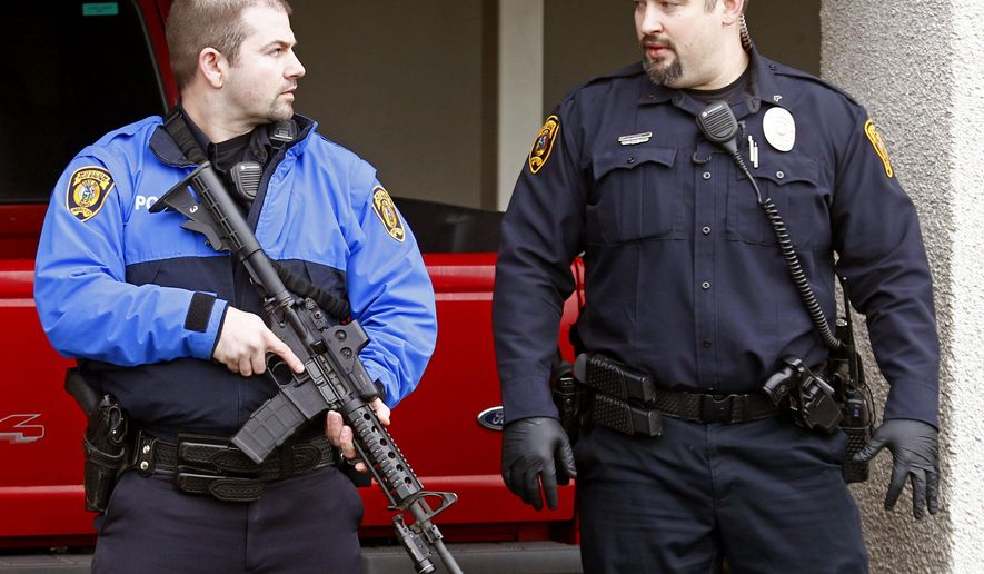 Police officers talk ouside while emergency medical technicians aid one of the shooting victims in Moscow, Idaho, on Saturday, Jan. 10, 2015. Police say a gunman killed three people and critically wounded another during a spree at three locations in Moscow, Idaho. (AP Photo/Moscow-Pullman Daily News, Geoff Crimmins)