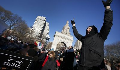 "An attendee symbolically holds a pen in the air while chanting ""Je Suis Charlie"" as several hundred people gather in solidarity with victims of two terrorist attacks in Paris, one at the office of weekly newspaper Charlie Hebdo and another at a kosher market, in New York's Washington Square Park, Saturday, Jan. 10, 2015. (AP Photo/Jason DeCrow)"