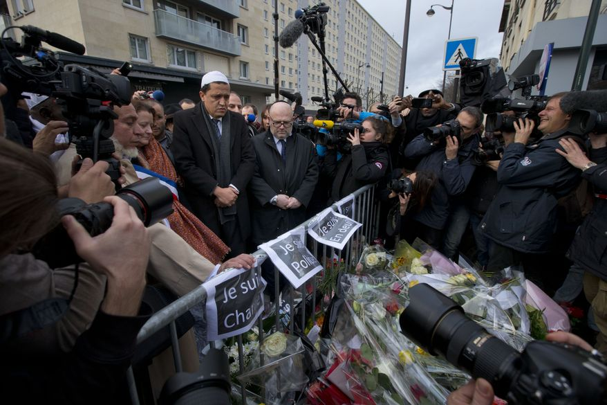 Hassen Chalghoumi, the Imam of Drancy mosque, center left with white cap, and an unidentified Rabbi, center right, pay their respects after placing flowers at a makeshift memorial outside a kosher grocery store where four hostages were killed on Friday, in Paris, Saturday, Jan. 10, 2015. (AP Photo/Peter Dejong)