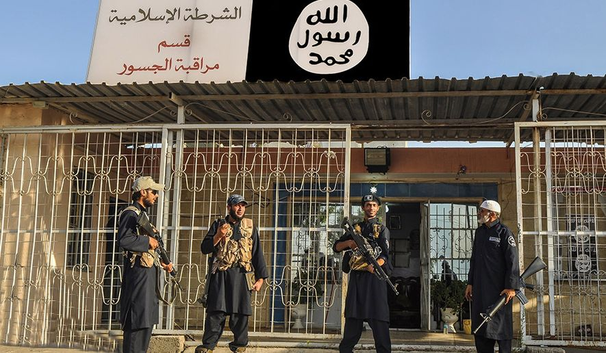 In this undated file photo posted on a militant website on Friday, Sept. 19, 2014, which has been verified and is consistent with other AP reporting, Islamic State group policemen stand guard in front of a police station in Nineveh province, Iraq. (AP Photo via militant website, File)