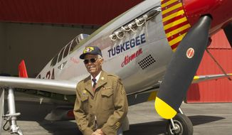 """This April 7, 2011, photo by Bruce Talamon shows Clarence E. """"Buddy"""" Huntley Jr., a member of the Tuskegee Airmen, the famed all-black squadron that flew in World War II, posing with a P-51C Mustang fighter plane similar to the one that he was a crew chief on while overseas during the war, at Torrance, Calif., Airport. Huntley and fellow Tuskegee Airman Joseph Shambrey, lifelong friends who enlisted together, both died on the same day, Monday, Jan. 5, 2015, in their Los Angeles homes, relatives said Sunday, Jan. 11, 2015. (AP Photo/Bruce Talamon (c) 2011 All Rights Reserved) ** FILE **"""