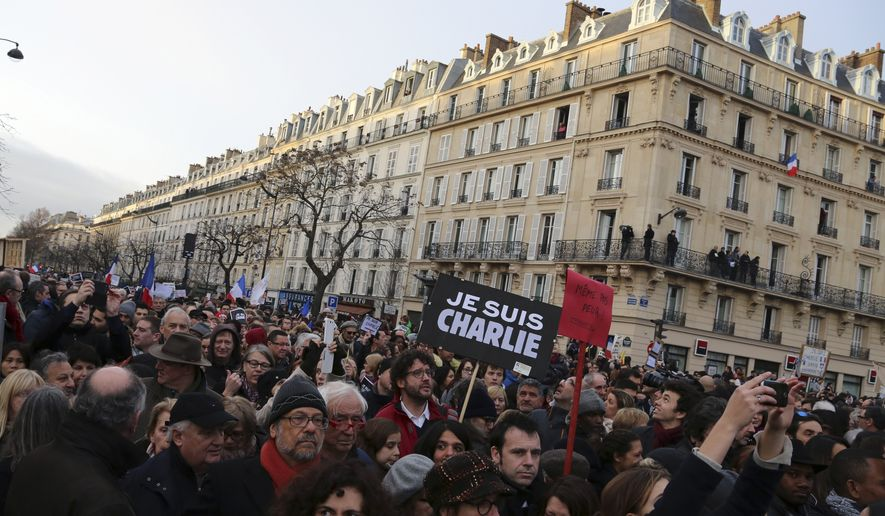 "Thousands of people wave national flags and hold placards that read ""I am Charlie"" at the Place de la Nation in Paris Sunday, Jan. 11, 2015. More than 40 world leaders, their arms linked, marched through Paris Sunday to rally for unity and freedom of expression and to honor 17 victims of three days of terrorist attacks. (AP Photo/Burhan Ozbilici)"