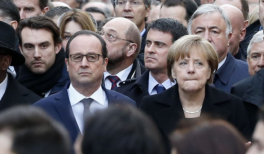 French President Francois Hollande and German Chancellor Angela Merkel march in Paris, France, Sunday, Jan. 11, 2015.  Thousands of people began filling France's iconic Republique plaza, and world leaders converged on Paris in a rally of defiance and sorrow on Sunday to honor the 17 victims of three days of bloodshed that left France on alert for more violence. (AP Photo/Michel Euler)