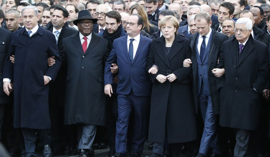 Front from the left, Israeli Prime Minister Benjamin Netanyahu, Malian President Ibrahim Boubacar Keita, French President Francois Hollande, German Chancellor Angela Merkel, EU Council President Donald Tusk and Palestinian Authority President Mahmoud Abbas, process arm-in-arm in Paris, France, Sunday, Jan. 11, 2015.  Thousands of people began filling France's iconic Republique plaza, and world leaders converged on Paris in a rally of defiance and sorrow on Sunday to honor the 17 victims of three days of bloodshed that left France on alert for more violence. (AP Photo/Michel Euler)