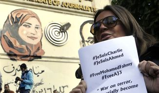 Marwa Omara, the fiancée of jailed Al-Jazeera English journalist Egyptian-Canadian Mohammed Fahmy, holds a paper that quotes him and calls for his freedom from an Egyptian jail, as she participates in a show of solidarity with the victims of Wednesday's attack in Paris on the Charlie Hebdo newspaper, at the Press Syndicate in Cairo, Egypt, Sunday, Jan. 11, 2015. (AP Photo/Amr Nabil)