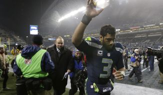 Seattle Seahawks quarterback Russell Wilson runs off the field after an NFL divisional playoff football game against the Carolina Panthers in Seattle, Saturday, Jan. 10, 2015. The Seahawks won 31-17. (AP Photo/Elaine Thompson)