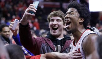 Rutgers forward Kadeem Jack (11) takes a selfie with a fan after defeating Wisconsin in an NCAA college basketball game, Sunday, Jan. 11, 2015, in Piscataway, N.J. Rutgers won 67-62. Jack had 20 points for Rutgers. (AP Photo/Mel Evans)
