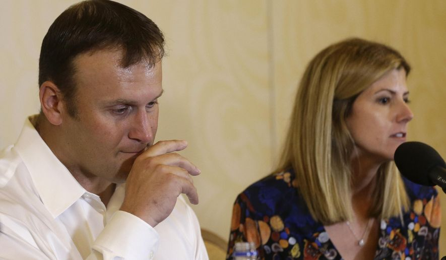 Former Miami Dolphins fullback Rob Konrad, left, listens while his wife Tammy, right, responds to a question during a news conference where he told about his ordeal of swimming nine miles to shore after he fell off his boat while fishing last week off the South Florida coast, Monday, Jan. 12, 2015, in Plantation, Fla. Konrad fell off his 36-foot-boat while fishing alone. The boat was on auto pilot and floated away. (AP Photo/Lynne Sladky)