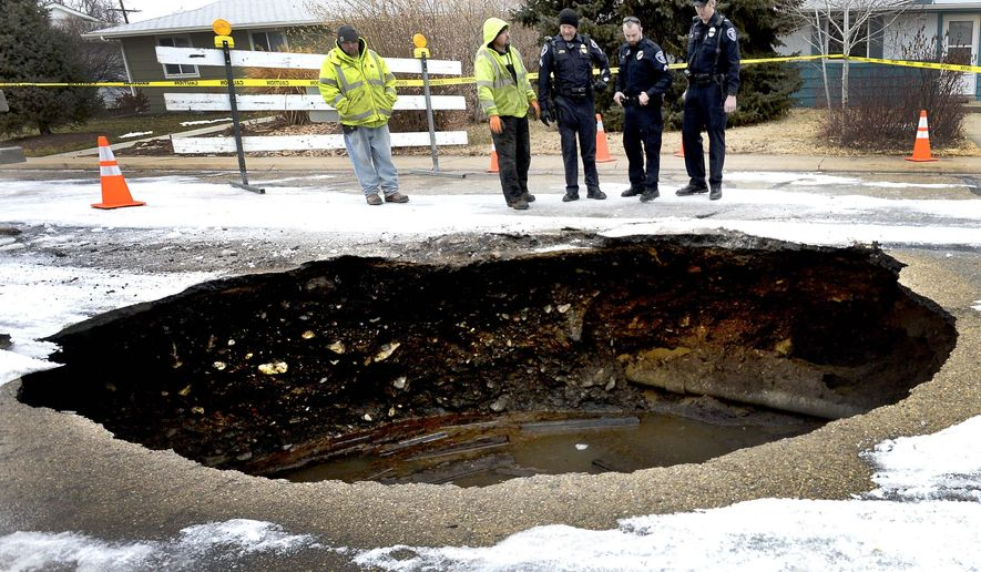Members of Lafayette Public Works and the Lafayette Police Department look over a large sink hole on East Cleveland Street in Lafayette, Colo., Monday, Jan. 12, 2015. (AP Photo/Boulder Daily Camera, Mark Leffingwell)